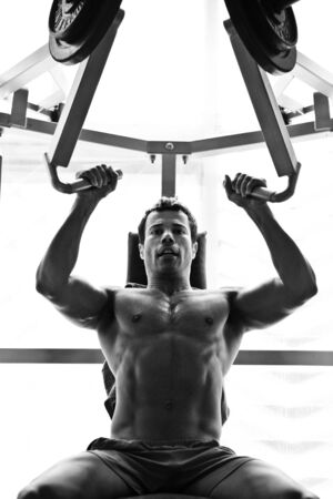 artistic shot, black and white, of a young bodybuilder hard training in the gym  shoulder press photo