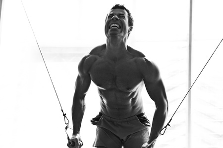 artistic shot, black and white, of a young bodybuilder hard training in the gym  cable crossover