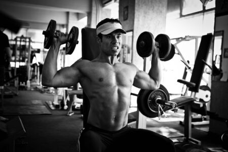 artistic shot, black and white, of a young bodybuilder hard training in the gym  dumbbell shoulder press photo
