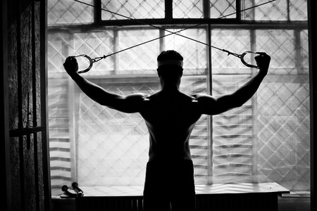 artistic shot, black and white, of a young bodybuilder hard training in the gym  shoulders - rear cable crossover photo