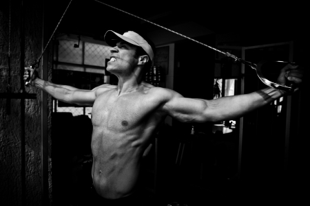 artistic shot, black and white, of a young bodybuilder hard training in the gym  shoulders - rear cable crossover