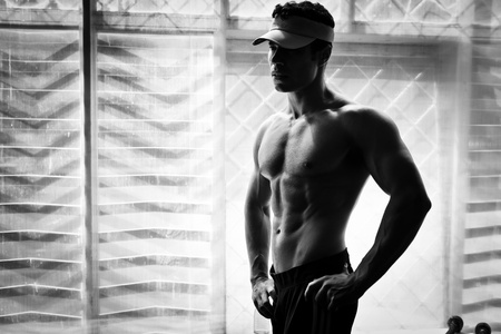 six pack abs: artistic shot, black and white, of a young bodybuilder posing in the gym