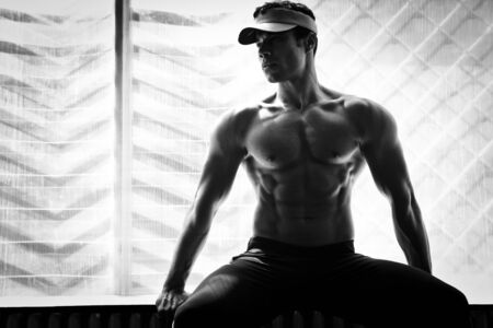 artistic shot, black and white, of a young bodybuilder posing in the gym photo