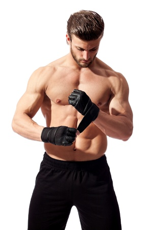 young fit man putting his gloves, preparing for training