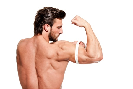 handsome fit young man measuring his arm with centimeter