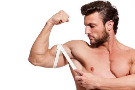 flexion: handsome fit young man measuring his arm with centimeter