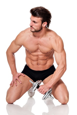 young fit man holding a dumbbell, on white background, seated, looking to the left photo