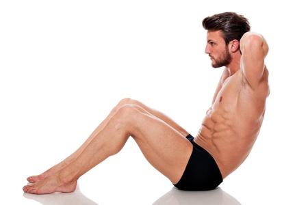 abdominal fitness: hombre joven en forma, entrenando sus abdominales: Crunch, sobre fondo blanco