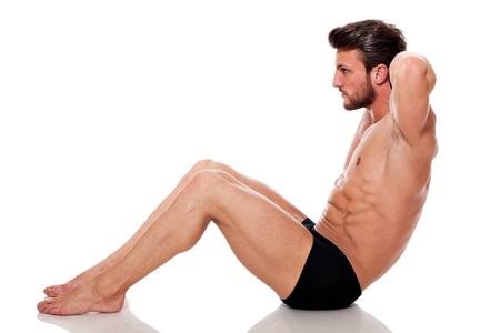 young fit man, training his abs: crunch, on white background Stock Photo