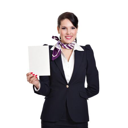 Beautiful dark haired young business woman dressed in a navy suit with a purple scarf holding a blank sheet of cardboard in her right hand, isolated on white background
