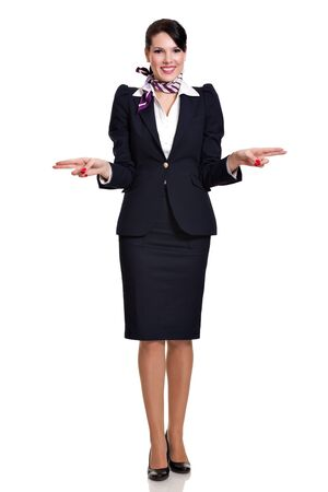 Beautiful dark haired young steward woman dressed in a dark blue suit with a purple scarf standing and showing the side exits of a plane, isolated on white background Stock Photo