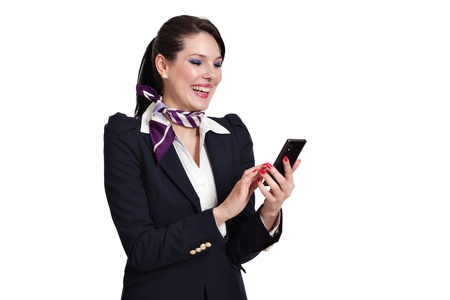 Beautiful dark haired young business woman dressed in a navy suit with white shirt and a purple scarf standing laughing checking her mobile phone, isolated on white background photo