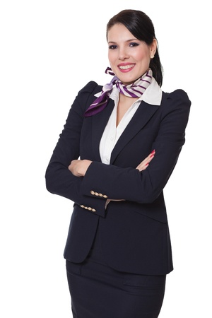 Beautiful dark haired young business woman dressed in a navy suit with a purple scarf and white shirt standing smiling and holding her arms crossed, isolated on white background