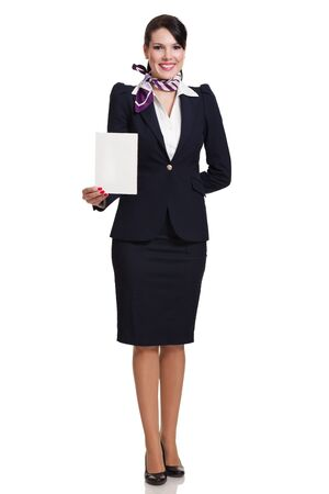 Beautiful dark haired young business woman dressed in a navy suit with a purple scarf standing and holding a blank sheet of cardboard in her right hand, isolated on white background photo