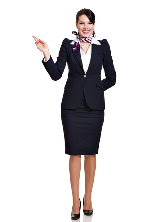 Beautiful dark haired young business woman dressed in a dark blue suit with a purple scarf standing and showing to her upper right side with two fingers, isolated on white background