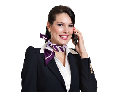 Beautiful dark haired young business woman dressed in a dark blue suit with a purple scarf smiling and talking to desktop phone held in her left hand, isolated on white background
