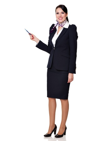 Beautiful dark haired young business woman dressed in a navy suit with a purple scarf and white shirt standing smiling and showing to upper left with her pen, isolated on white background
