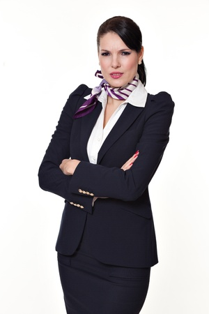 intrigued: Beautiful dark haired young business woman dressed in a navy suit with a purple scarf and white shirt standing serious and intrigued and holding her arms crossed, isolated on white background