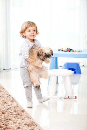blond boy: child playing with his dog in the living room