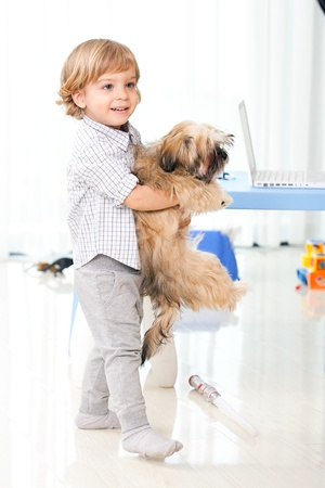 child playing with his dog in the living room photo