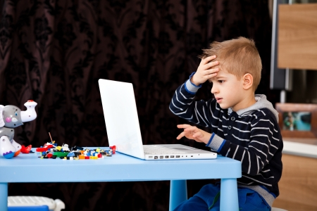 child looking at his laptop at home making a mistake