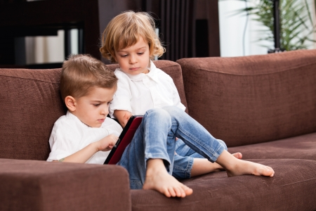 five year: Two small children with a tablet, on the sofa Stock Photo