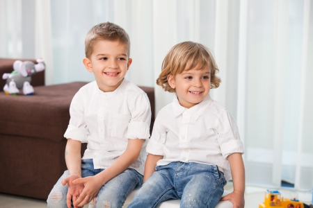 blue jeans kids: Two happy small children sitting and smiling