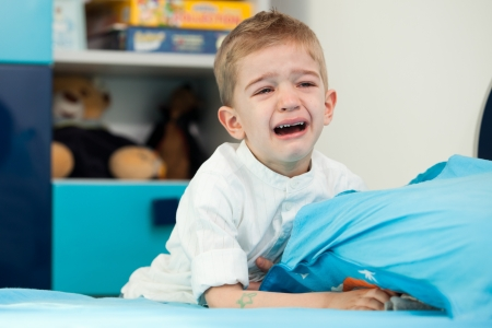 A sad five year old child sitting next to his bed with holding a pillow and crying 免版税图像