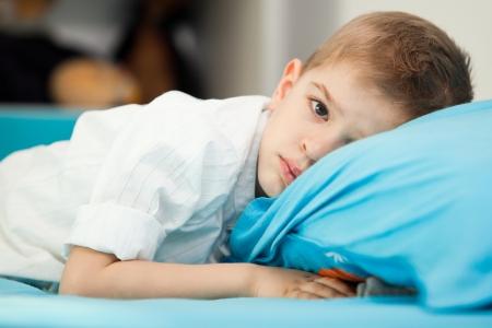 sad look: Un niño triste cinco años sentado en su cama con la cabeza sobre una almohada azul