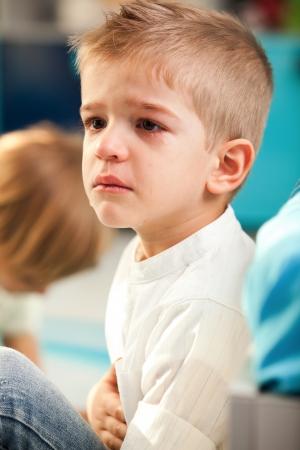 dolor de estomago: Un niño de cinco años que tiene un dolor abdominal Un niño de cinco años que tiene un dolor en el vientre y el llanto Foto de archivo