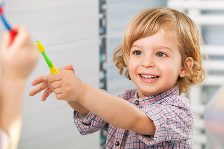 two year old: A two year old child passing a toothbrush to someone in the bathroom Stock Photo