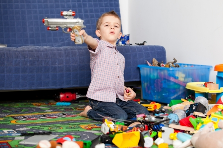 gun room: A five year old child playing in his room with a lot of toys around him  A five year old boy pointing at something someone with his toy gun