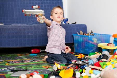 habitacion desordenada: Un ni�o de cinco a�os que juega en su habitaci�n con un mont�n de juguetes a su alrededor un ni�o de cinco a�os que apunta a algo a alguien con su pistola de juguete