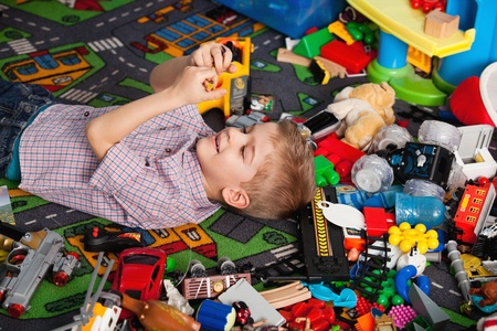 A five year old child playing in his room with a lot of toys around him Reklamní fotografie - 20673148