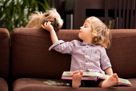lap dog: A two year old child sitting on the sofa with a book in his lap feeding his little dog