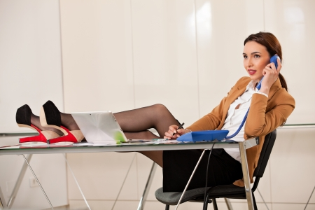 young beautiful business woman smiling and talking on the phone with her legs on the desk and a pen in her hand photo