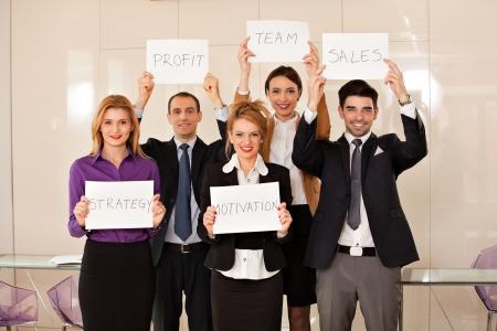 empleados trabajando: equipo de j�venes empresarios que sostienen cartones estrategia, motivaci�n, beneficios, equipo, ventas