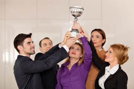 job satisfaction: young team holding a trophy; happy business people celebrating their victory