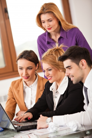 Young beautiful business woman smiling with a laptop in front of her and three colleagues business people around her