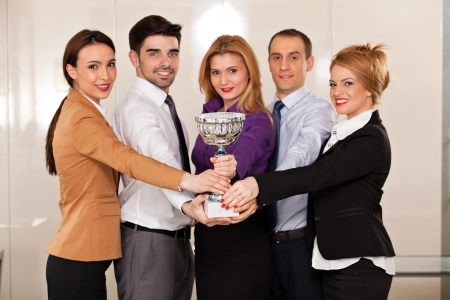 young team holding a trophy; happy business people celebrating their victory, focus on the trophy Reklamní fotografie - 23378803