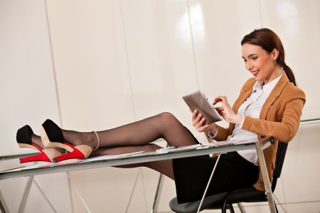 young beautiful business woman smiling and plying on her tablet with her legs on the desk photo