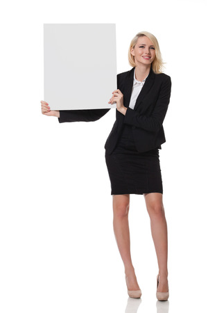 full length of a beautiful young blonde woman standing and holding a board to her right side photo
