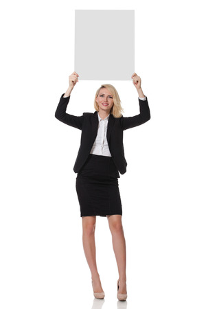 full length of a beautiful young blonde woman standing and holding up a board photo