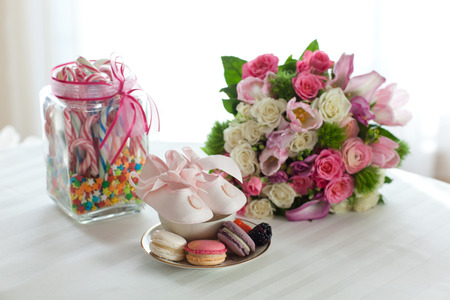 Coloured arrangement of macaroons, candy flowers for a little girl baptism party photo