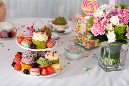 Coloured beautiful arrangement of cupcakes, fruits, candy and flowers on a table photo