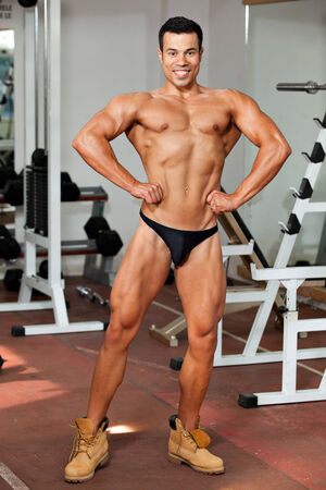 young bodybuilder in the gym, posing, front lat spread photo