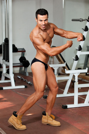 young bodybuilder in the gym, posing. photo