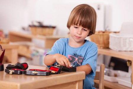 Child playing with musical instruments toys at his table; Image shot from a kindergarten photo