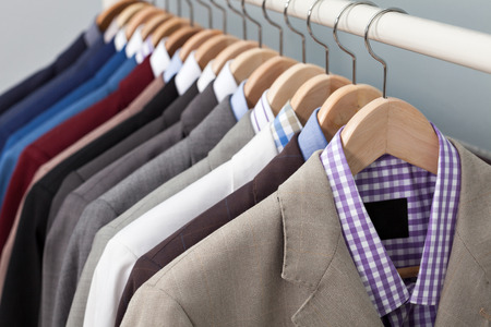 Closeup of the upper section of a row of man suits in a closet on hangers Archivio Fotografico