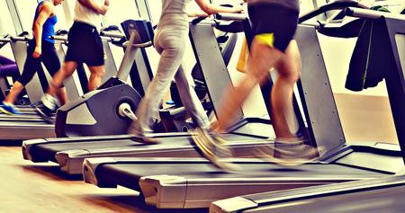 corriendo: retro tiro, vintage gimnasio - la gente que se ejecutan en m�quinas, cinta de correr Foto de archivo